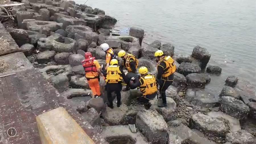 一名男子遺體在竹圍漁港南堤被釣客發現,警消獲報後將遺體運上岸。(邱立雅翻攝)