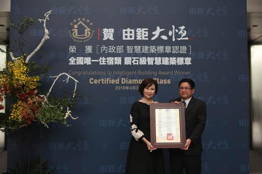 (由鉅建設董事長林嘉琪(左)22日接受營建署長吳欣修頒發「鑽石級智慧建築」證書。圖:曾麗芳)