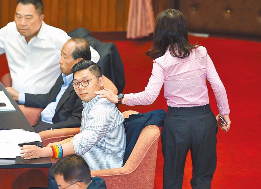 傳有中常委揚言撤銷挺同立委提名,國民黨團總召江啟臣昨嗆「你若要拉下提名,就拉我吧!」圖為表態支持同婚的藍委許毓仁(左下),手上戴著彩虹顏色的護腕出現在議場,同黨立委林奕華(右)拍了拍他的肩膀。(本報資料照片)