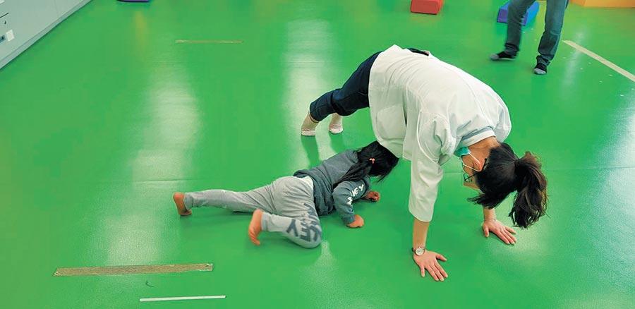 以肌肉能力较不足、不太喜欢动的小朋友为例,可以跟他一起玩一些游戏,如:小牛耕田、大法师、火车过山洞等。(杨汉声摄)