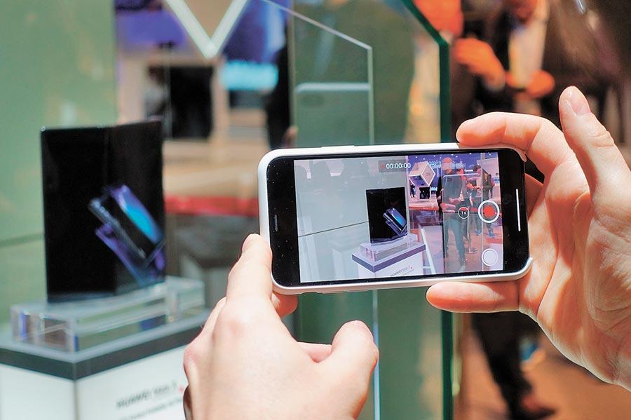 華為Mate X搭載的多模5G晶片被譽為「華為最強」。圖為2月25日,參觀者在西班牙世界移動通信大會拍攝華為Mate X手機。(新華社)