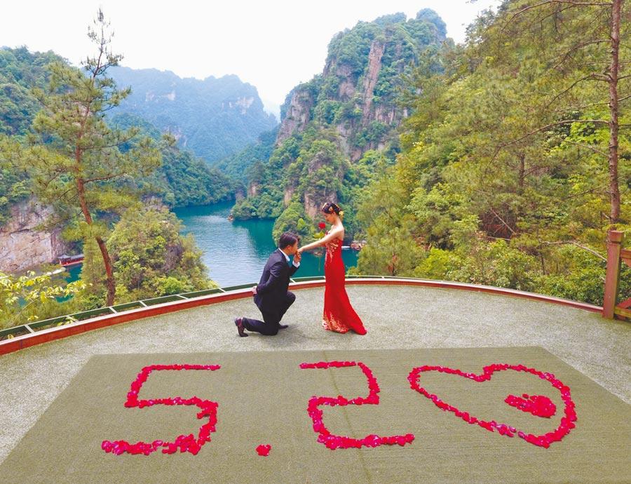 一對情侶選擇在5月20日這一天表達愛意,於湖南張家界寶峰湖風景區拍照留念。 (新華社資料照片)