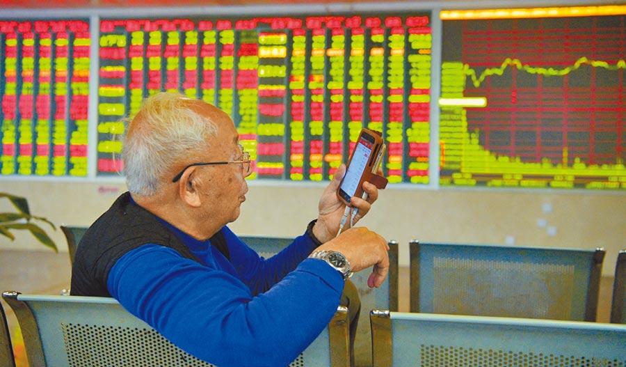 四川成都,某證券營業部大廳內的股民用手機查詢個股走勢。(中新社資料照片)