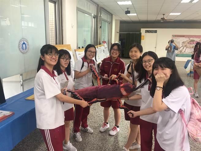 女學生克服恐懼,與大型蟑螂道具拍照合影。(王文吉攝)
