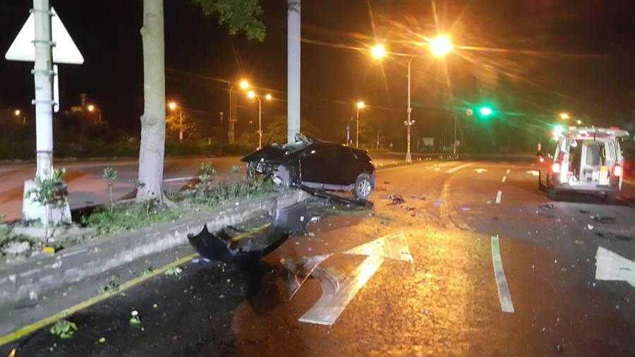 黑色轎車騎上分隔島撞路桿,車體嚴重變形。(巫靜婷翻攝)