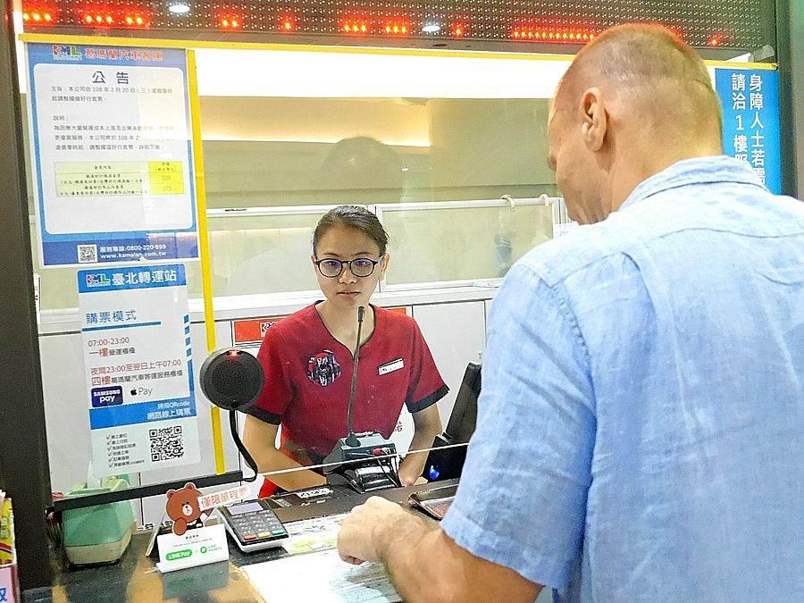 外籍老師在台北轉運站與售票口工作人員互動。(國發會提供)