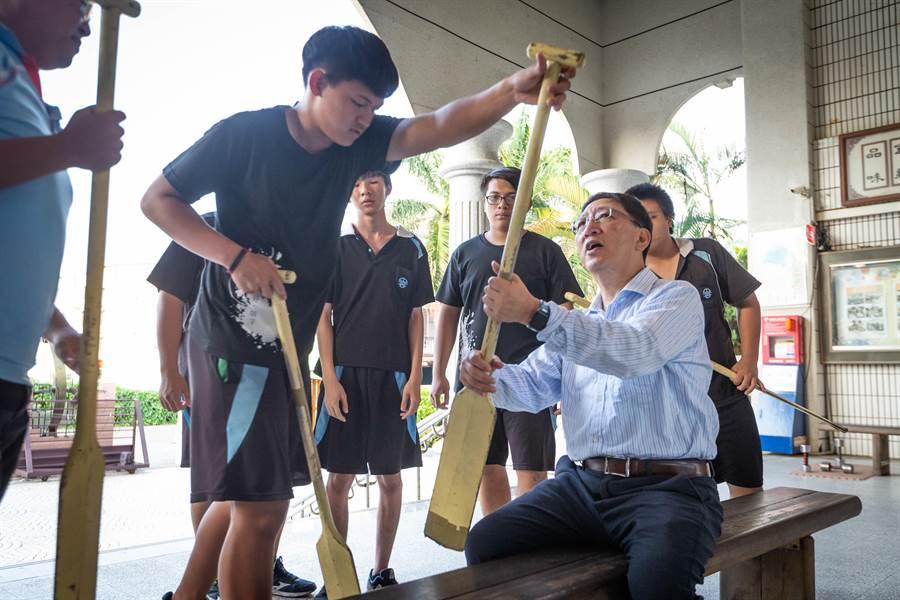 教育局長吳榕峯與中芸國中龍舟隊學生討教傳統龍舟與競技龍舟划槳的不同之處。(袁庭堯攝)