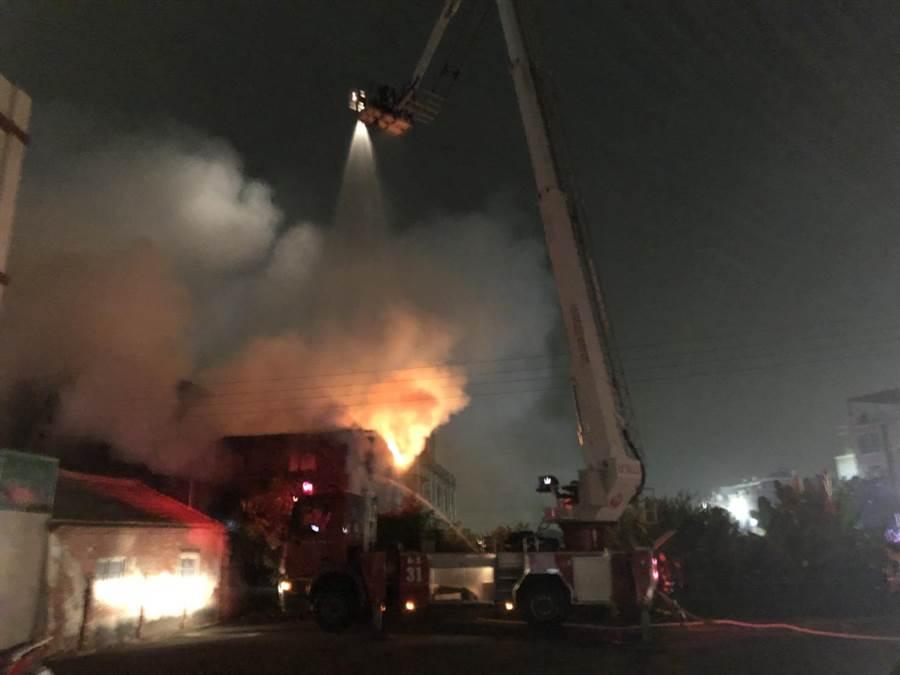 彰化縣消防局為緊急滅火,奮勇架起10高的雲梯,搭起水管,在高空中形成一個超級大水龍頭灑水澆滅地面失火的水龍頭工廠。(吳敏菁翻攝)