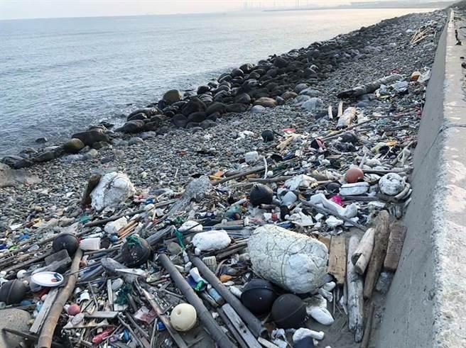 垃圾及漂流木隨海浪沖上苑港漁港沿岸。(巫靜婷翻攝)