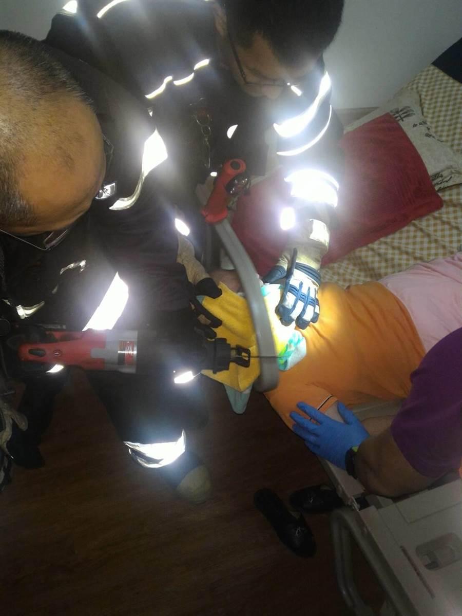 婦人頭卡照護床動彈不得,消防員搶救脫困。(消防局提供)
