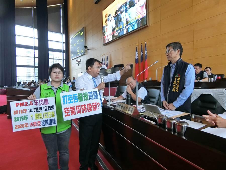 台中市議員張玉嬿(左起)、謝志忠24日在質詢時,拿著「空汙減量承諾書」希望環保局承諾2020年PM2.5濃度達到15微克。(盧金足攝)