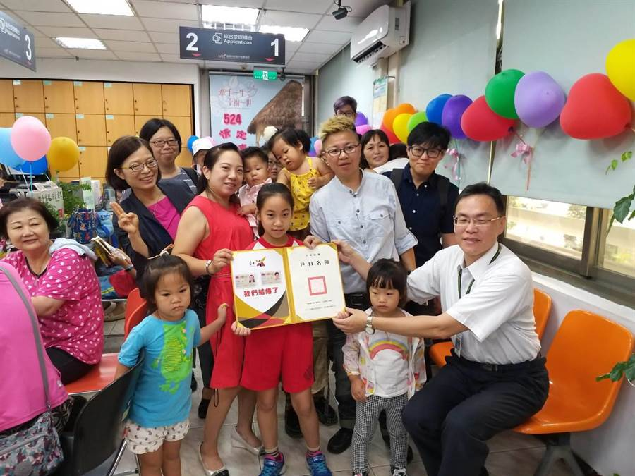 穆德(金髮者)與陳釩(紅衣削肩者)帶著四個小孩到東區戶政事務所登記結婚。(台南市民政局提供)