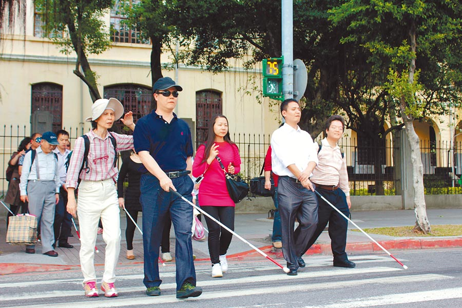 視障者過馬路,各類車輛若不禮讓,最高可罰7200元。圖為伊甸基金會邀大陸盲人協會體驗台北街頭。(伊甸基金會提供)