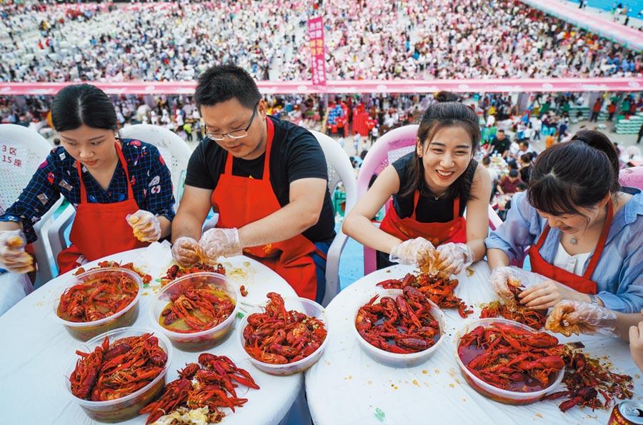 2018年6月13日,食客在江蘇盱眙都梁公園品嘗小龍蝦。(新華社)