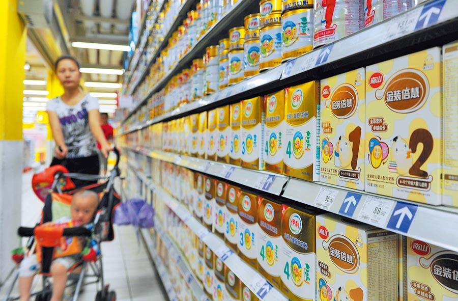 在湖南長沙一超市內,一位母親推著嬰兒選購奶粉。(中新社資料照片)