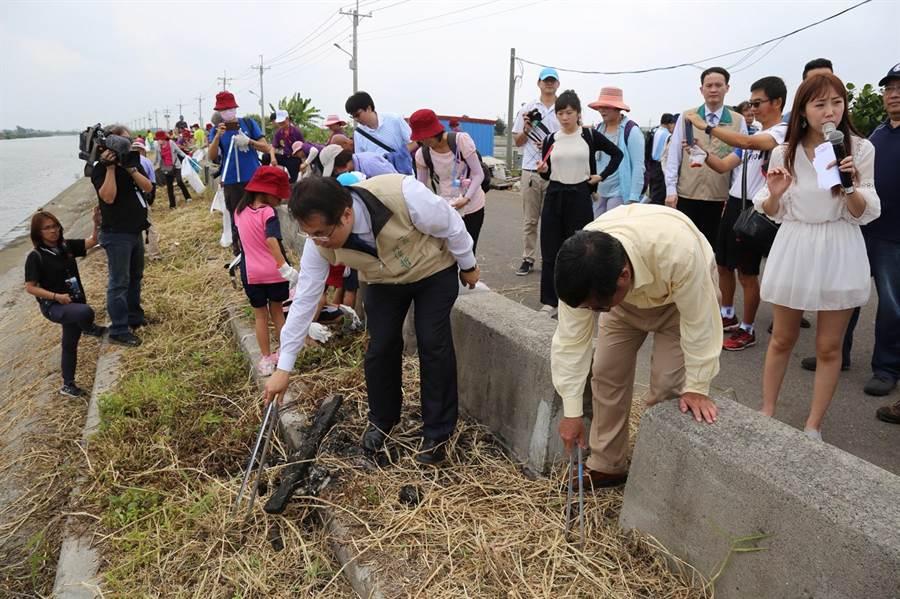 台南市長黃偉哲25日跟著志工撿拾鹿耳門溪垃圾。(程炳璋攝)