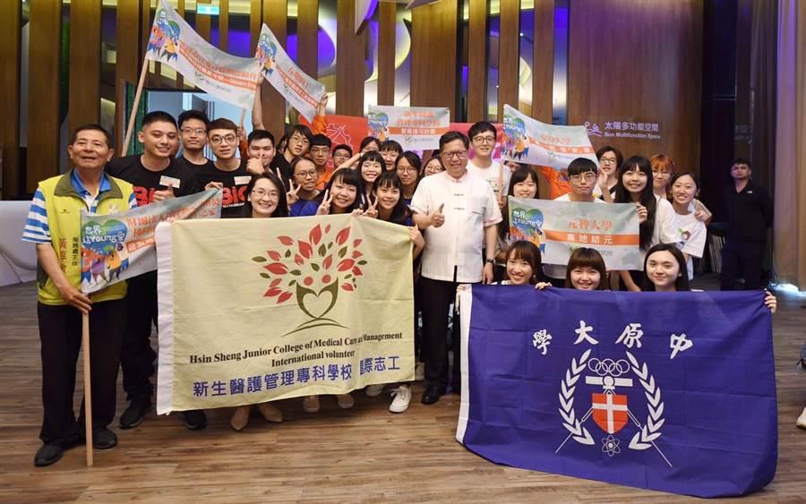 來自各校的21組國際志工團隊,25日在興光堡壘由市長鄭文燦(中)授旗熱血出發,揭開暑期青年國際志工服務序幕。(甘嘉雯攝)