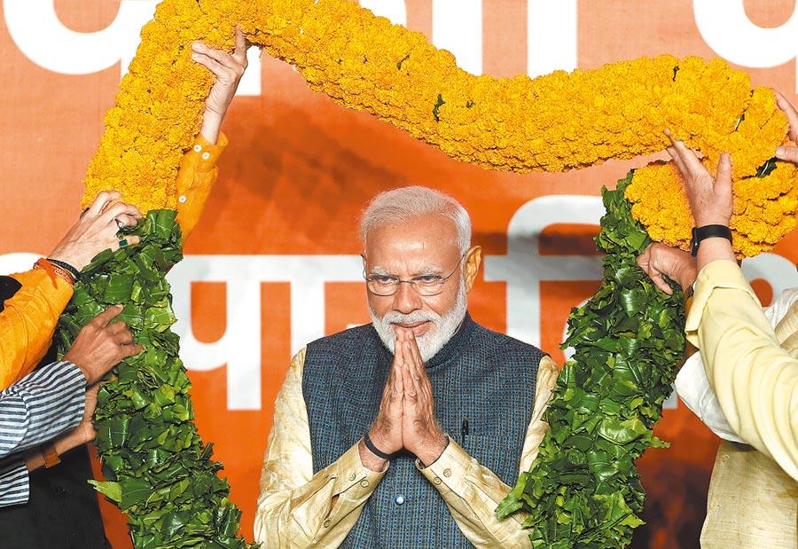 莫迪贏得大選後,接受印人黨贈送的花環(路透)。陸印兩國專家一致認為,莫迪連任有利保持陸印關係穩定。