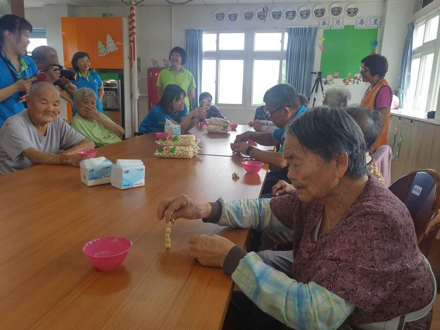 白河日照中心提前舉辦活動慶端午,除了包粽子外,還用當地特產蓮子取代雞蛋,玩起立蛋活動,也藉機訓練老人家注意力及手指靈活度。(莊曜聰攝)
