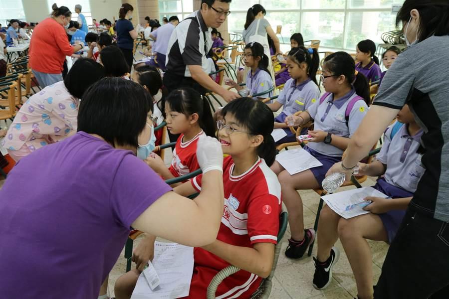 嘉義縣國小學童潔牙觀摩比賽,牙醫師檢測潔牙度。(廖素慧攝)