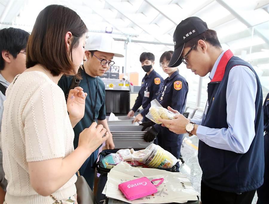 幾名從韓國搭機抵達桃園機場的旅客,隨身行李正接受檢查。(范揚光攝)