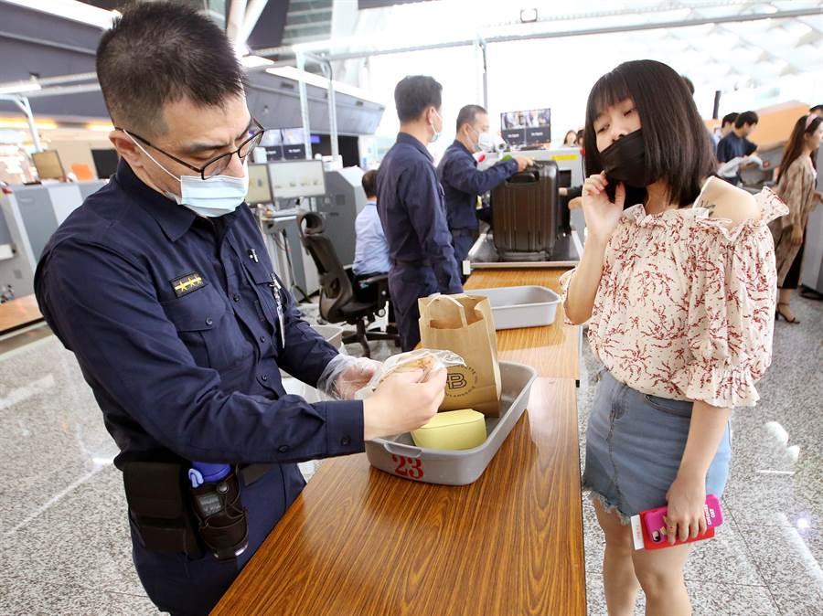 1名從韓國搭機抵達桃園機場的旅客,隨身行李正接受詳細檢查。(范揚光攝)