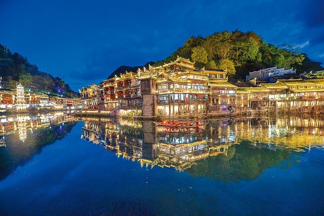 湖南湘西鳳凰古城沱江沿岸燈火璀璨,遊客行走在古城中,仿佛置身夢境。(中新社)
