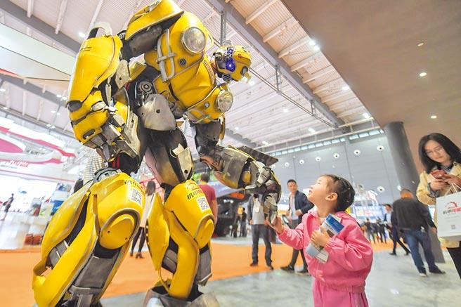 2019年5月15日,在長沙國際工程機械展覽會上,小朋友和機器人互動。(新華社)