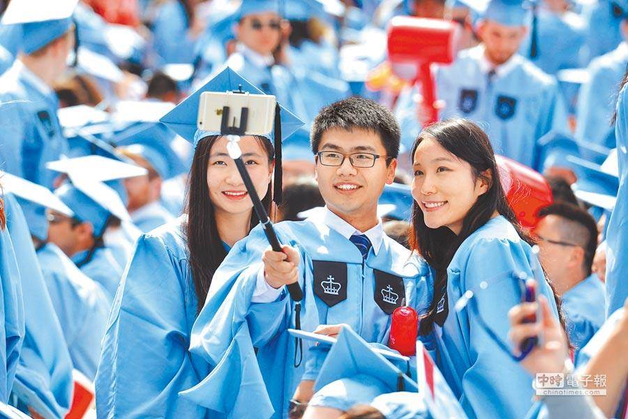這是2015年美國哥倫比亞大學舉行畢業典禮時,來自大陸的留學生正在自拍。(新華社)