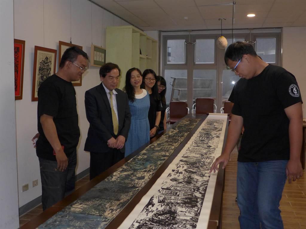 勤益科大機械工程系學生羅啟羅(右)講解他們刻畫的「勤益版清明上河圖」內容景緻。(林欣儀攝)