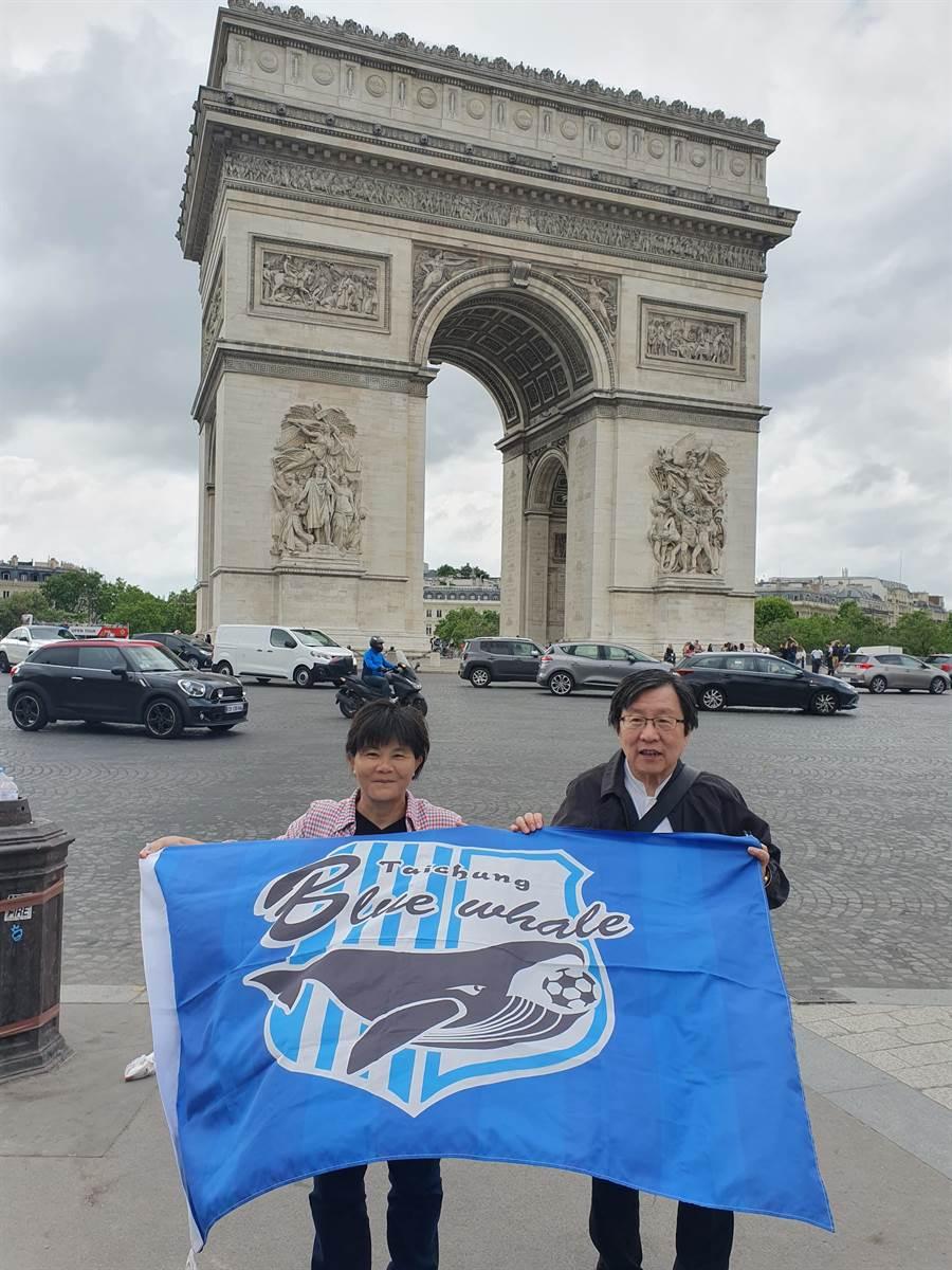 中華足協理事長邱義仁(右)、副理事長呂桂花至巴黎參加國際足總年會,還在凱旋門前拿台中藍鯨的隊旗合照。(中華足協提供)