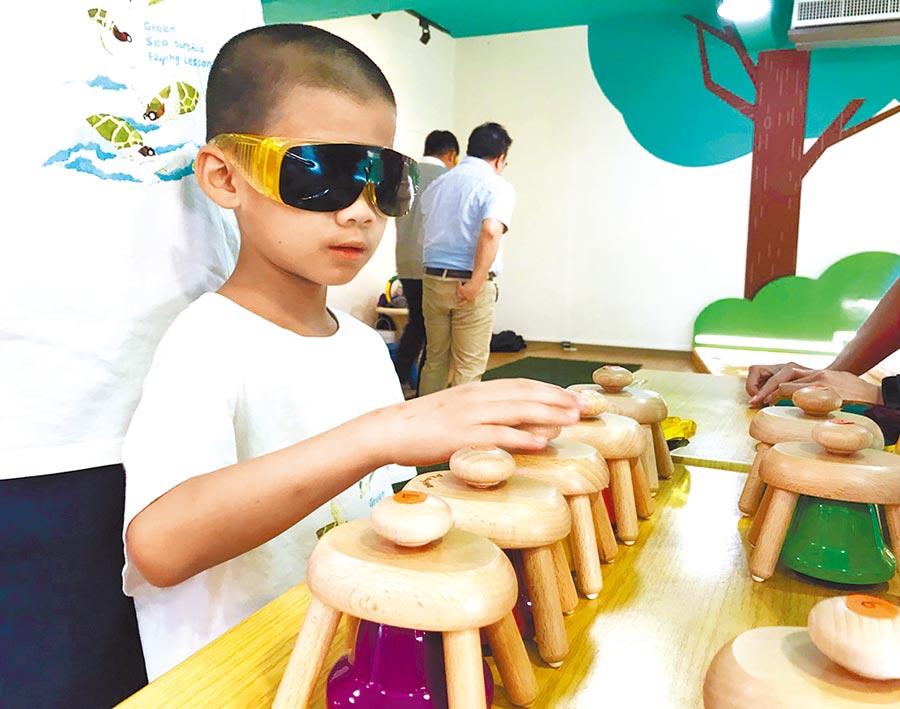 鶯歌分館的遊戲室提供融合視障、聽障、自閉症等族群的遊戲玩具,圖為小朋友體驗視障遊戲過程。(王揚傑翻攝)
