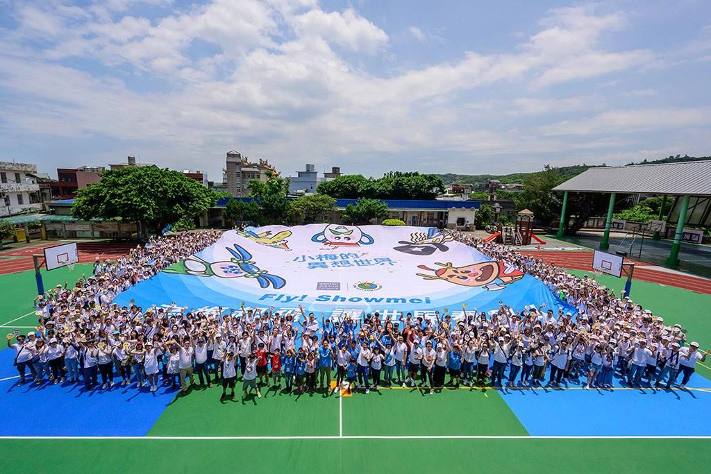 電通安吉斯集團全體員工與老梅國小師生共同撐開「小梅的異想世界」共創精靈大旗幟。