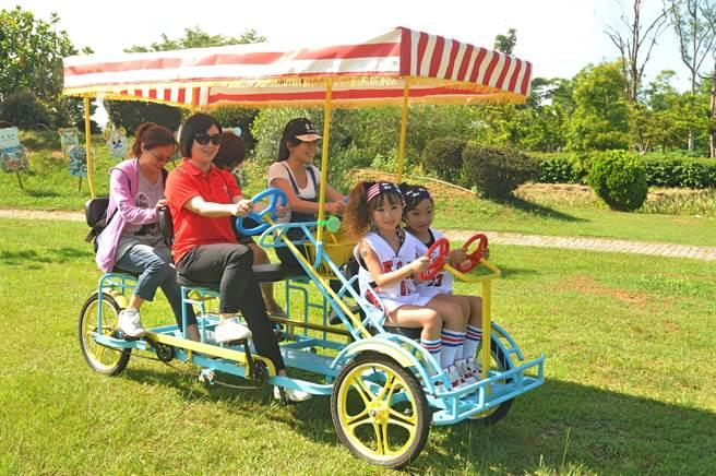 騎協力車徜徉在茵茵草地上,也是夏日遊金門的樂趣之一。(李金生攝)