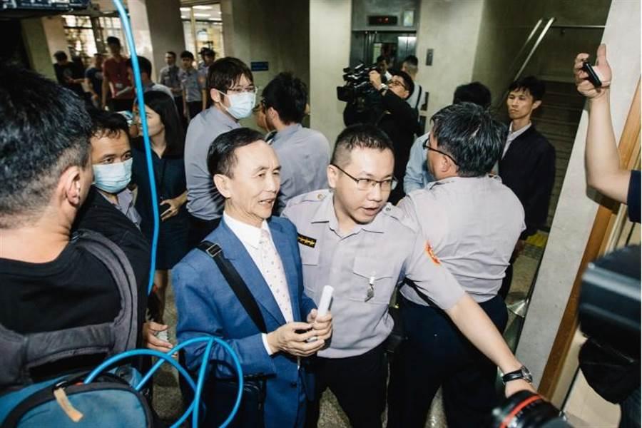 台北地檢署4日傳喚媒體人吳子嘉(前左2)出庭說明,一位支持韓國瑜的民眾對吳舉標語抗議,隨即遭法警架開。(資料照片,郭吉銓攝)