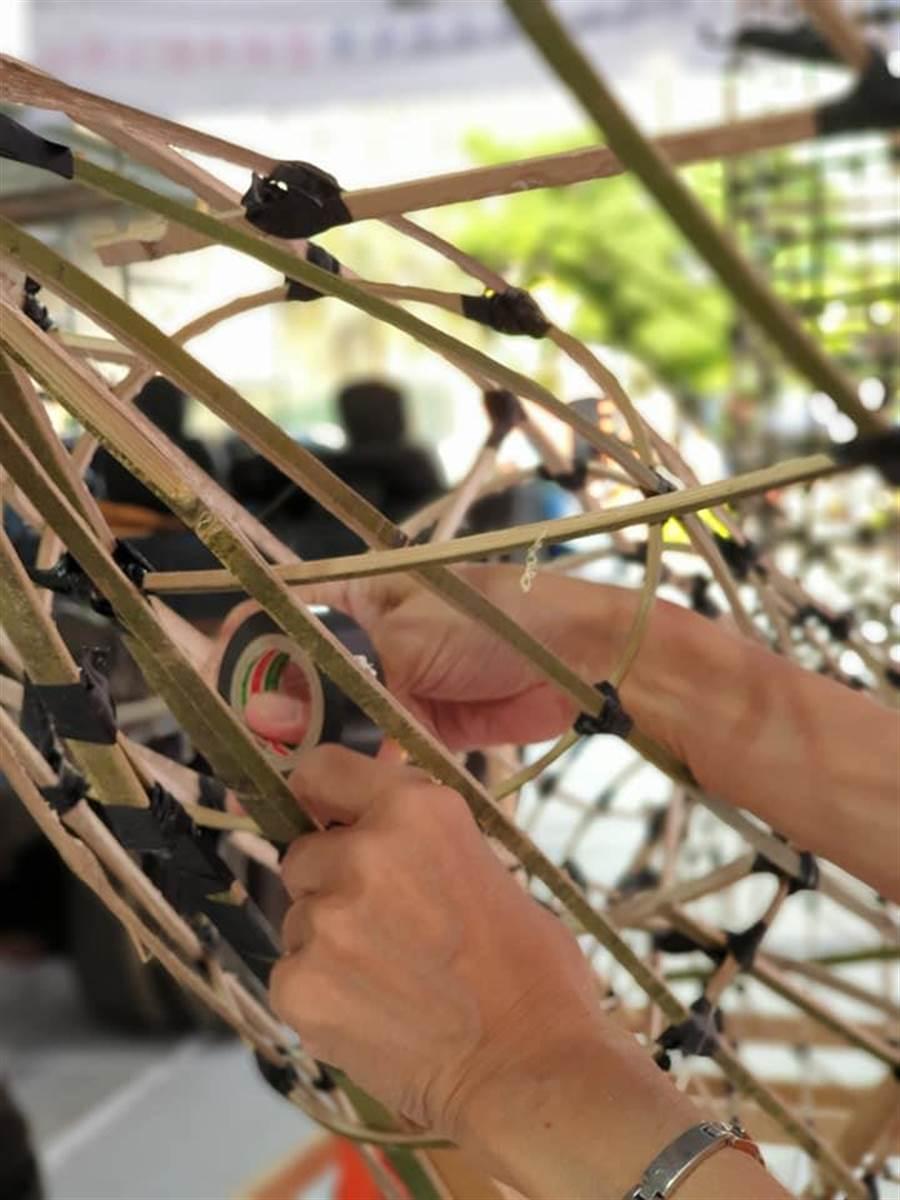 社區阿伯獨具匠心以一根一根的竹子,熟練地編織魚偶。(基隆市文化局提供)