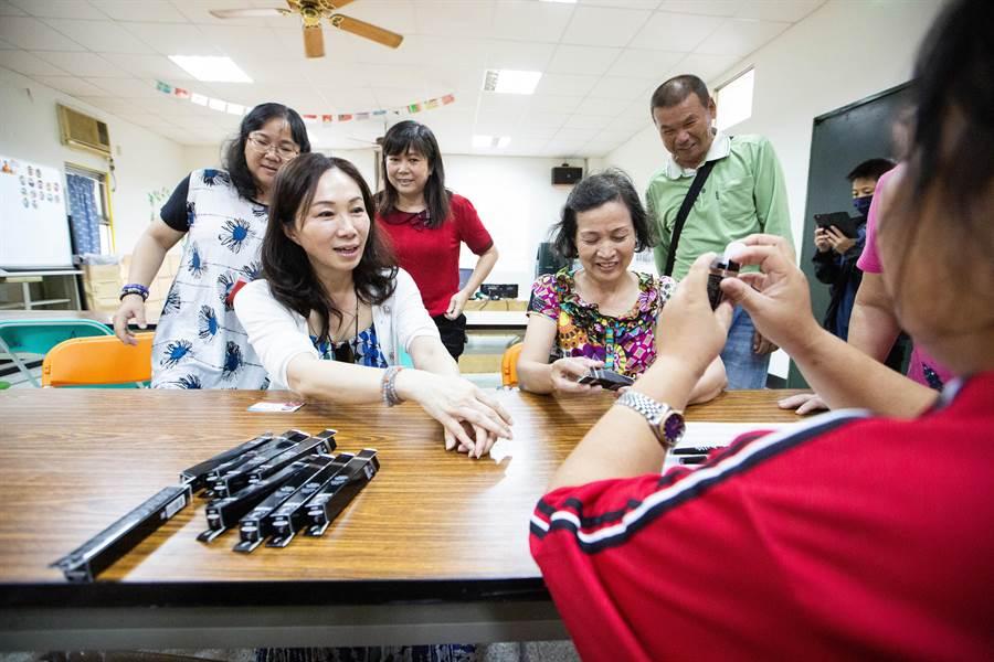 工坊學員正努力進行睫毛膏商品包裝,李佳芬直接請益學員,也跟著動手試做。(袁庭堯攝)