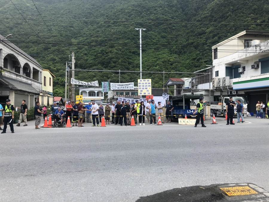 環保局今在和平村舉辦水泥窯代燒公聽會,場外數十名居民舉牌抗議。(張祈翻攝)