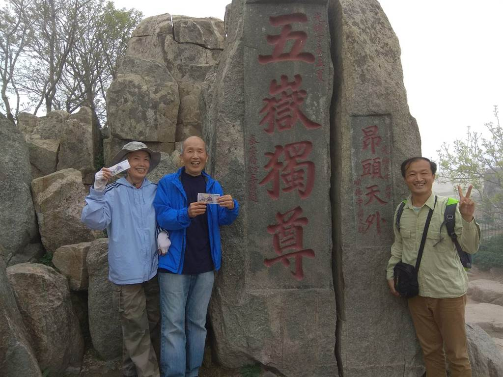 手持人民幣5元背面的五嶽獨尊,與泰山五嶽獨尊的摩崖石刻合影。(作者提供)