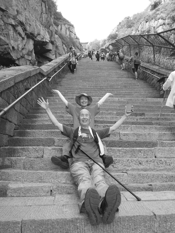 作者父母以七八十歲高齡登泰山,在十八盤上、接近南天門處興奮合影。(作者提供)