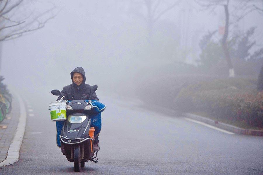 霧霾中的機車騎士。(中新社資料照片)