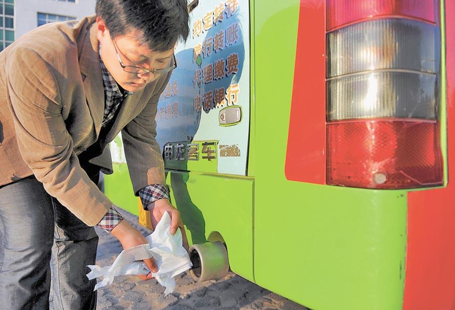 一名工作人員用紙巾展示液化天然氣公車的廢氣排放情況。(新華社資料照片)