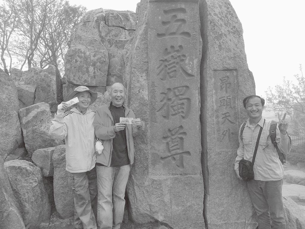 手持人民幣5元背面的五嶽獨尊,和摩崖石刻合影。(作者提供)