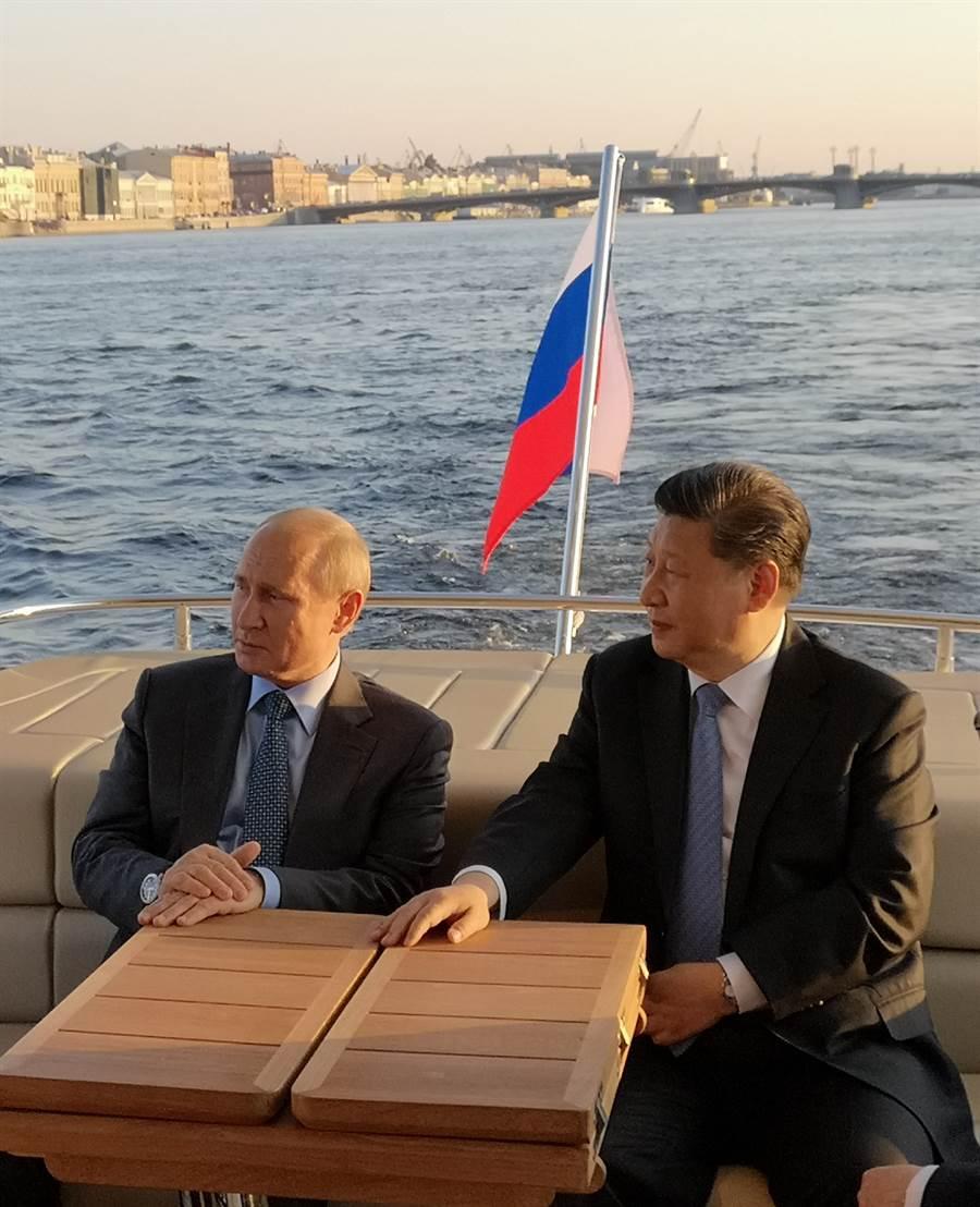 習近平與普丁在聖彼得堡共同乘船遊覽涅瓦河。聖彼得堡是普丁的家鄉,他向習近平介紹當地風土人情和沿途建築。(圖/新華社)
