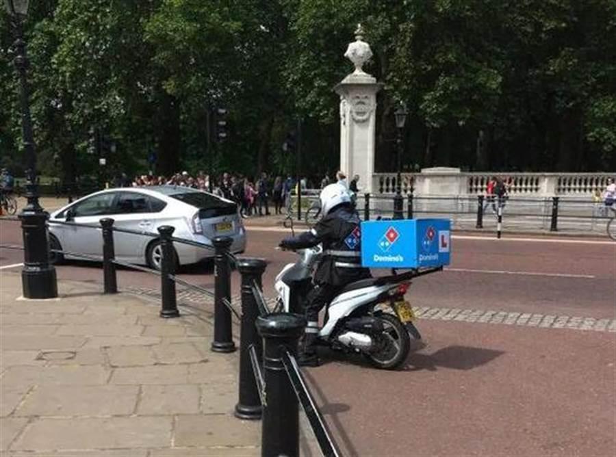 披薩外送小哥在白金漢宮前,被警衛欄查證實被騙了。(圖取自《太陽報》)