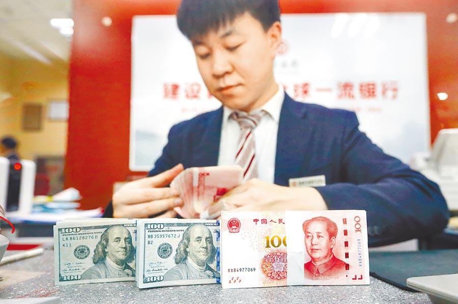 端午假期,香港離岸人民幣兌美元匯價創下一周以來最大單日跌幅。圖為山西省太原市一位銀行人員清點貨幣。(中新社)