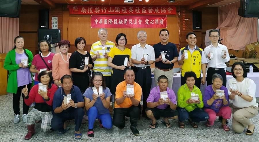 ▲中華國際投融資促進會捐贈二千包機能米,並與受贈的部份弱勢戶代表合影。(廖志晃攝)