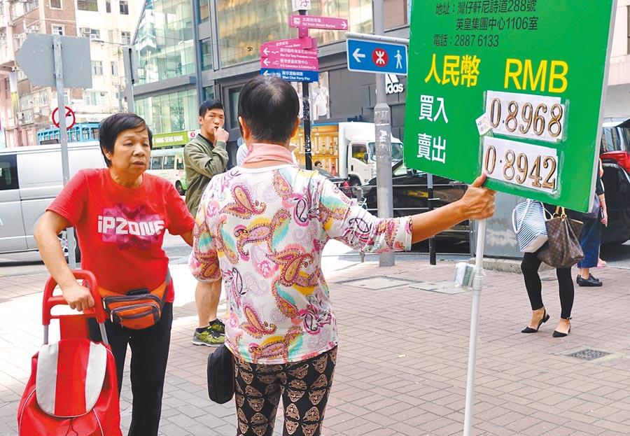 2018年10月31日,找換店職員在香港灣仔街頭舉牌招攬顧客。當天,人行宣布將招標發行2018年第一期和第二期央行票據。(中新社)