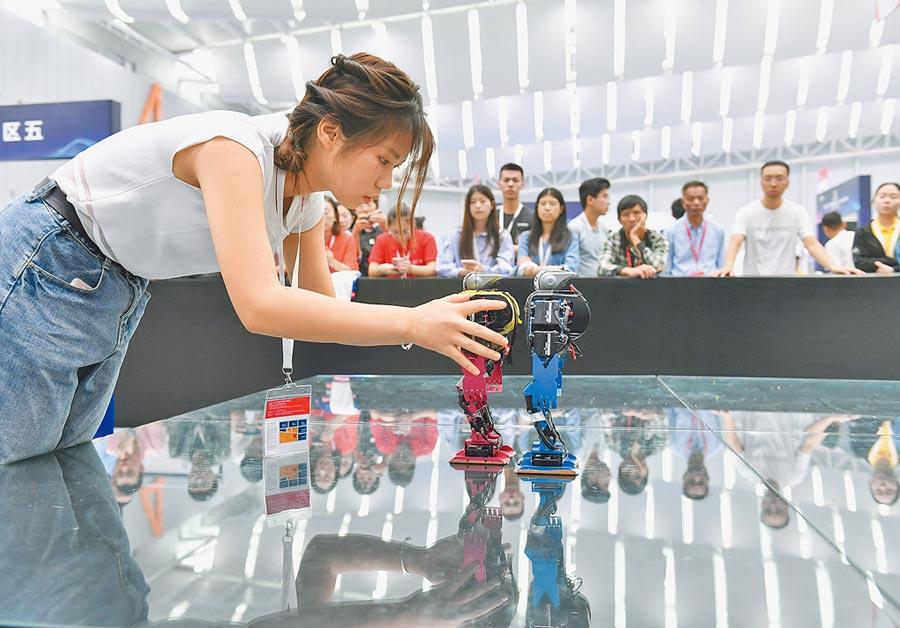 2018年10月25日,來自合肥工業大學的大二女生在第二十屆中國機器人及人工智能大賽前調試機器人。(新華社)