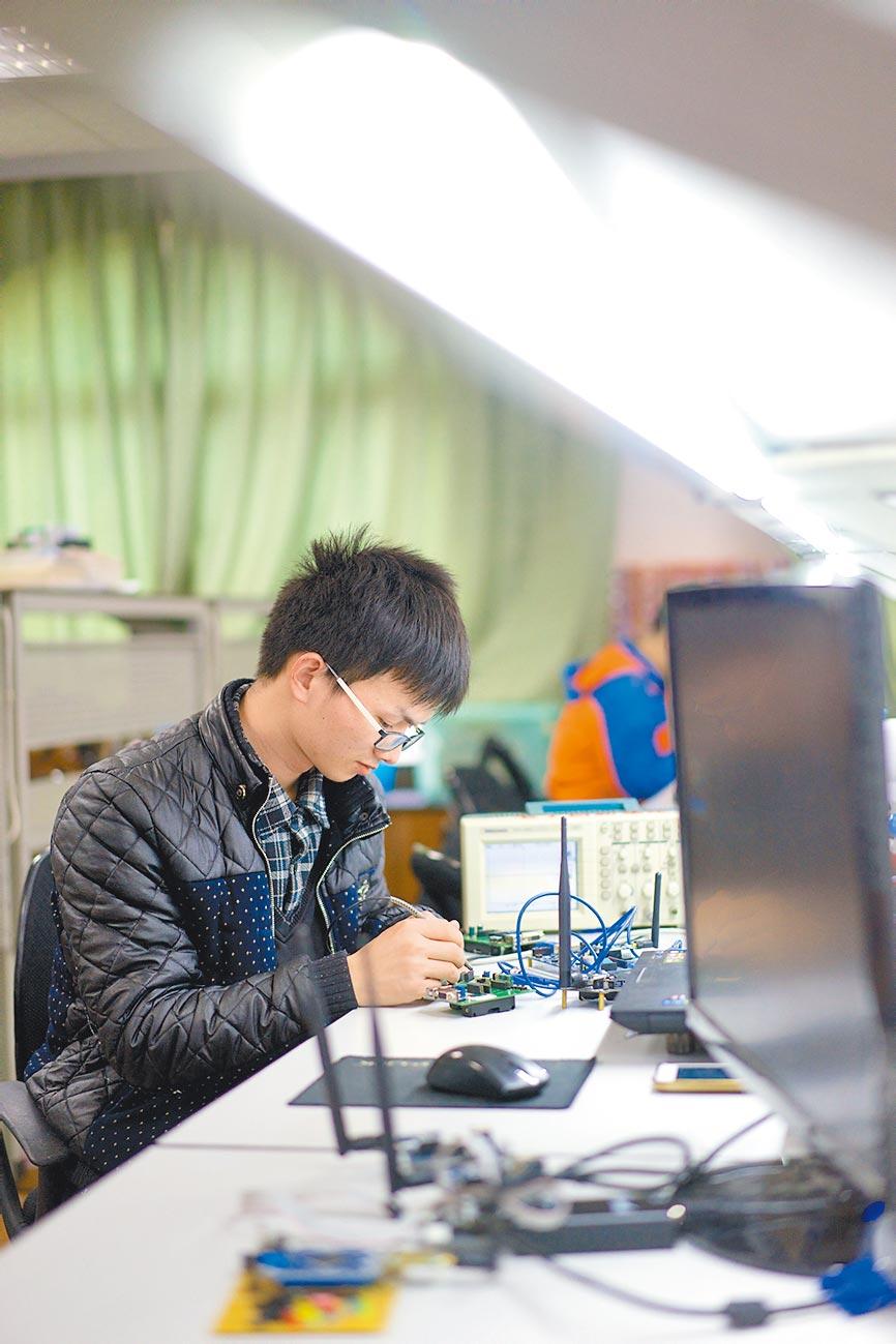 2016年3月23日,華東交通大學學生在實驗室內製作物聯網設備。(新華社)